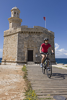 Spain, Menorca, Woman cycling through boardwalk at Ciutadella - DSF000501