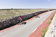 Spain, Menorca, Punta Nati, Man and woman cycling on road - DSF000506