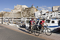 Spain, Menorca, Man and woman cycling through promenade in Ciutadella - DS000509