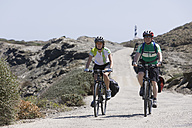 Spain, Menorca, Man and woman cycling, Cap de Favaritx in background - DSF000518