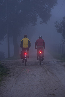 Italy, Tuscany, Mature men riding bicycle - DSF000492