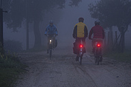 Italy, Tuscany, Men and woman riding bicycle - DSF000490