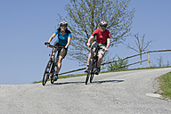 Germany, Bavaria, Man and woman riding bicycle - DSF000475