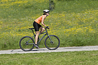Germany, Bavaria, Mid adult woman riding bicycle - DSF000467
