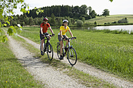 Germany, Bavaria, Man and woman riding bicycle - DSF000465