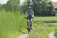 Germany, Bavaria, Mid adult woman riding bicycle - DSF000460