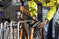 Germany, Bavaria, Munich, Mid adult woman locking bicycle - DSF000531