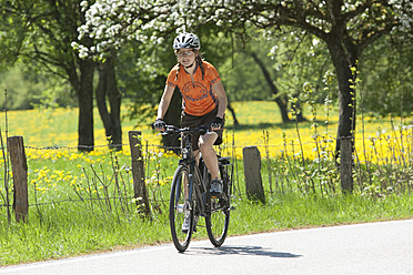 Germany, Bavaria, Young woman riding bicycle - DSF000541