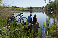 Germany, Bavaria, Man and woman sitting by bicycle - DSF000544