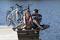 Germany, Bavaria, Man and woman sitting by bicycle - DSF000561