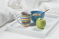 Tray of tea, apple and muesli on bed for breakfast, close up - CRF002173