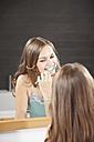 Germany, Bavaria, Young woman brushing teeth in bathroom - MAEF004582