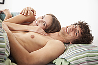 Germany, Bavaria, Young couple on bed, smiling, portrait - MAEF004610