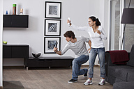 Germany, Bavaria, Young couple playing with game console - MAEF004637