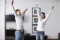 Germany, Bavaria, Young couple playing with game console - MAEF004623