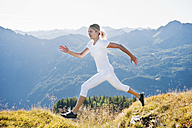 Austria, Salzburg County, Young woman running and jumping in alpine meadow - HHF004040
