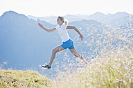 Austria, Salzburg County, Young woman running and jumping in alpine meadow - HHF004042