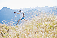 Austria, Salzburg County, Young woman with nordic walking pole and jumping in alpine meadow - HHF004044