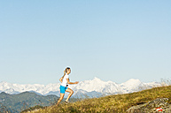 Austria, Salzburg County, Young woman running in alpine meadow - HHF004046
