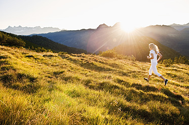 Austria, Salzburg County, Young woman running in alpine meadow - HHF004052