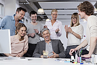 Germany, Bavaria, Munich, Men and women celebrating in office, smiling - RBYF000047