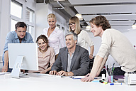 Germany, Bavaria, Munich, Men and women using computer in office, smiling - RBYF000104