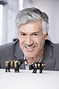 Germany, Bavaria, Munich, Mature man with bull and bear figurines, smiling, portrait - RBYF000057