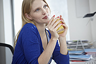 Germany, Cologne, Young woman with juice in apartment - RHYF000048