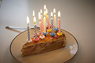 Germany, Cologne, Birthday cake with candles in apartment - RHYF000054