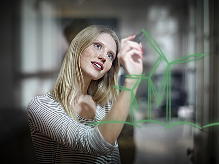 Germany, Cologne, Young woman drawing wind turbine on glass - RHYF000090