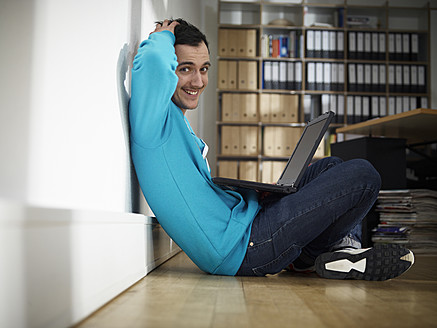 Germany, Cologne, Young man using laptop, smiling, portrait - RHYF000099