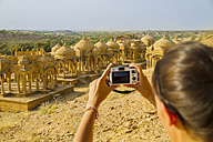India, Rajasthan,Jaisalmer, Female tourist photographing at Bada Bagh Cenotaphs - MBEF000316