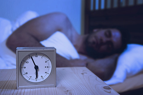 Alarm clock on table, man sleeping in background - RNF000959