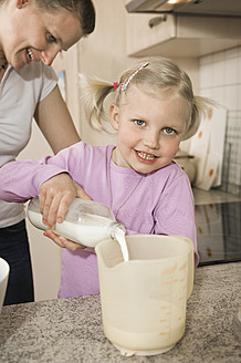Mother and daughter pouring milk into measuring cup - RNF000907