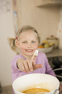 Girl showing finger covered with flour, smiling, portrait - RNF000915