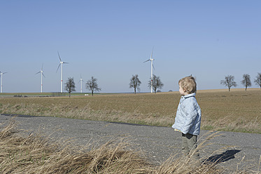 Germany, Saxony, Boy standing on road, wind turbine in background - MJF000016