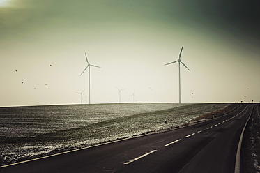 Germany, Saxony, View of empty road with wind turbine - MJF000012