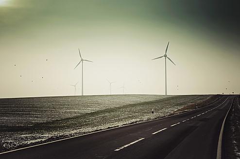 Germany, Saxony, View of empty road with wind turbine - MJF000012