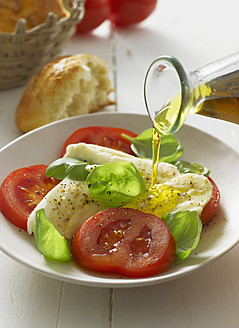 Olive oil pouring on caprese salad in plate, close up - KSWF000823
