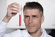 Germany, Bavaria, Munich, Scientist holding red liquid in test tube for medical research in laboratory - RBF000829