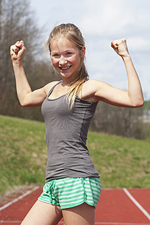 Austria, Teenage girl on track showing her muscles, smiling, portrait - WWF002309