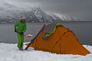 Norway, Skier removing snow with shovel near tent - FFF001304