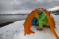 Norway, Lyngen, Skier in tent near polar sea - FFF001306