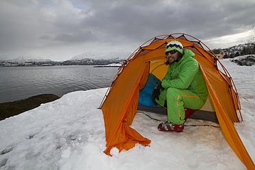 Norway, Lyngen, Skier in tent near polar sea - FFF001306