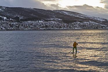 Norway, Narvik, Mature man paddling in polar ocean - FFF001288