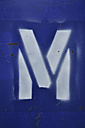 White spray paint letter M on blue, close up - AXF000025
