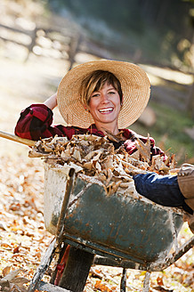 Austria, Salzburg County, Young woman in wheel barrow with autumn leaves, smiling - HHF004157