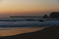 Portugal, Algarve, Sagres, View of beach with breaking waves at sunset - MIRF000428