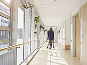 Germany, Cologne, Senior woman with walking frame at corridor in nursing home - WESTF018692