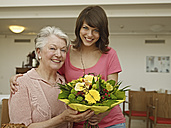Germany, Cologne, Women holding bouquet in nursing home, smiling, portrait - WESTF018701